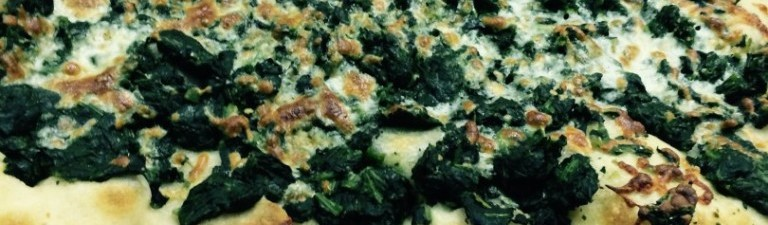 alt=pizza with spinach and mozzarella cheese